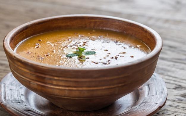 木製のテーブルのスパイシーなカボチャクリームスープのボウル