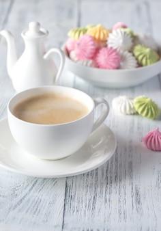 色のメレンゲとコーヒーのカップ