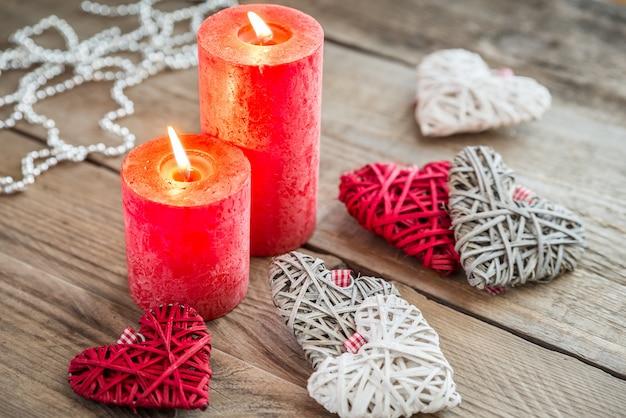Сердца с зажженными свечами на деревянной поверхности