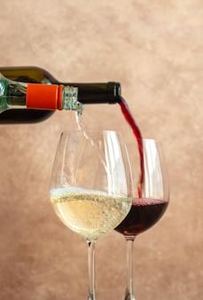 Белое и красное вино льется в бокалы