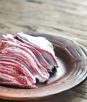 木製のテーブルに赤いベルベットのクレープケーキの部分
