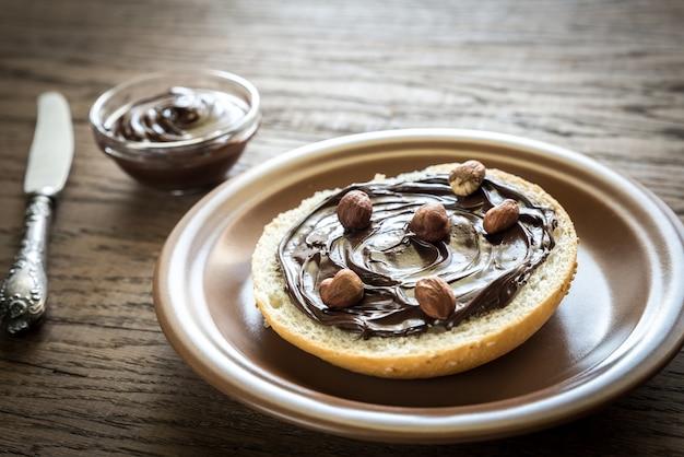 Булочка с кунжутом с шоколадным кремом и орехами