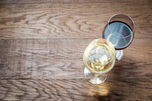 Бокалы с красным и белым вином на деревянном фоне