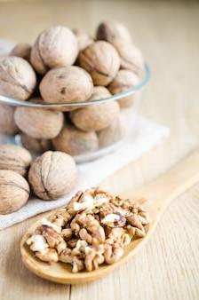 Грецкие орехи в стеклянной миске и деревянной ложке