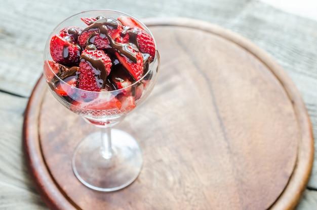 Свежая клубника под шоколадным топингом в стакане