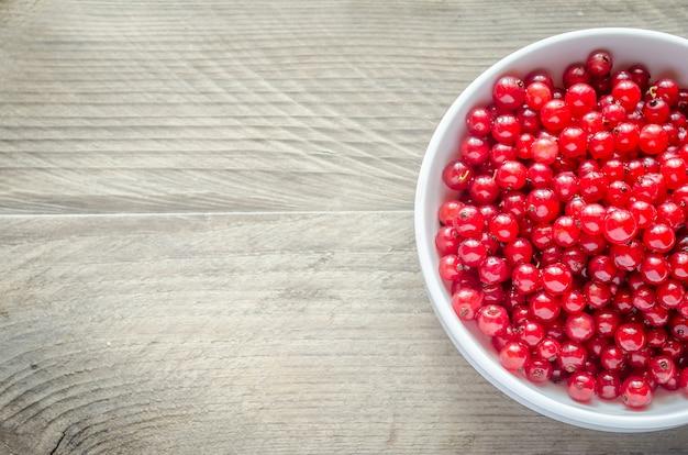 Чаша со свежей красной смородиной на деревянный стол
