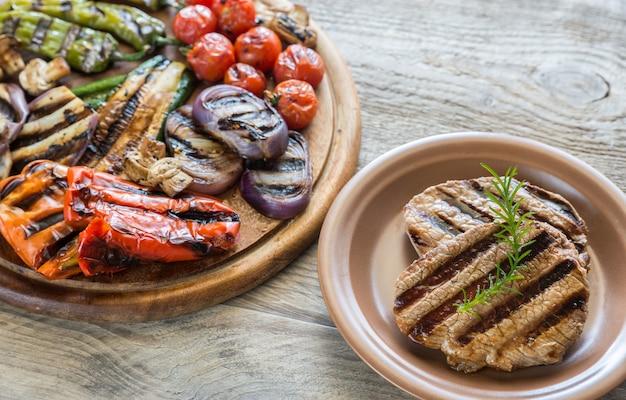 木の板にビーフステーキと野菜のグリル