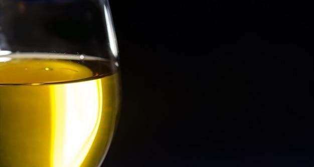 Белое вино в бокале на черном