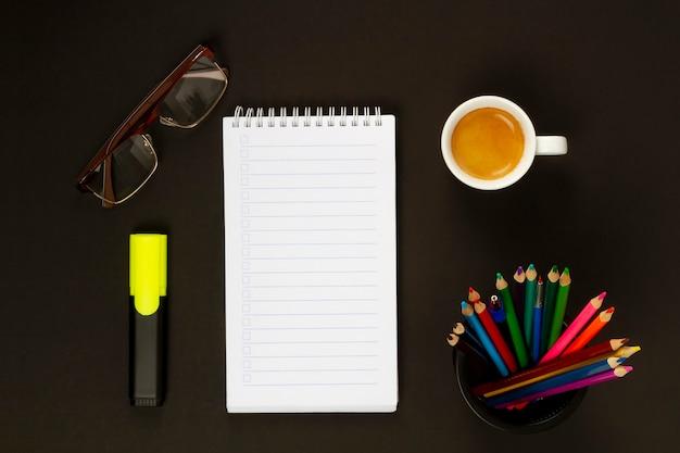 Чашка капучино, цветные карандаши, маркер, очки и блокнот на черном фоне. вид сверху.