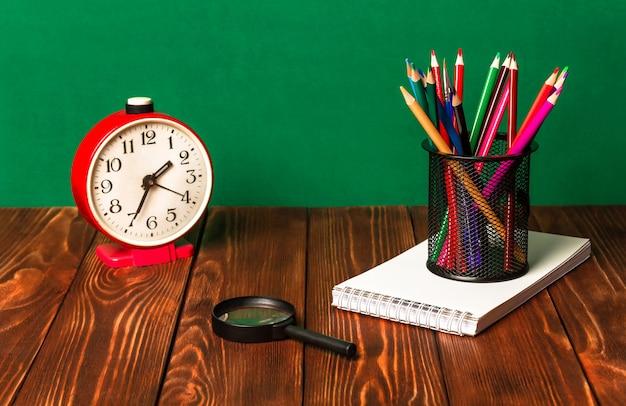 スタンド、ノート、目覚まし時計、木製のテーブルの上の虫眼鏡で色鉛筆。