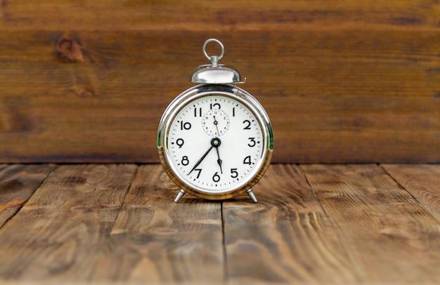Ретро будильник на коричневом деревянном столе.