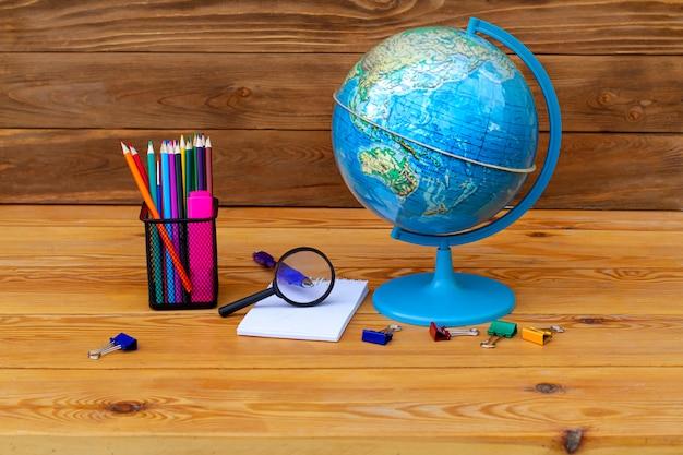 Обратно в школу! глобус, модель земли, учебный материал на деревянном столе на глобусе азии и австралии.