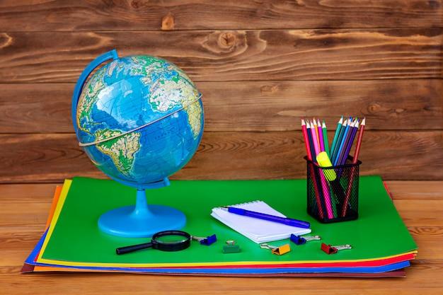学校に戻る!グローブ、地球モデル、木製のテーブルの教材。
