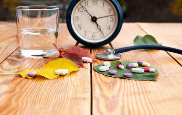 秋の風邪。薬を飲む時間。目覚まし時計、聴診器、カラフルな錠剤、木製のテーブルにさまざまな色の紅葉。