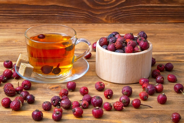Сушеные ягоды шиповника с чашкой ароматного напитка шиповника на дереве. целебные ягоды.