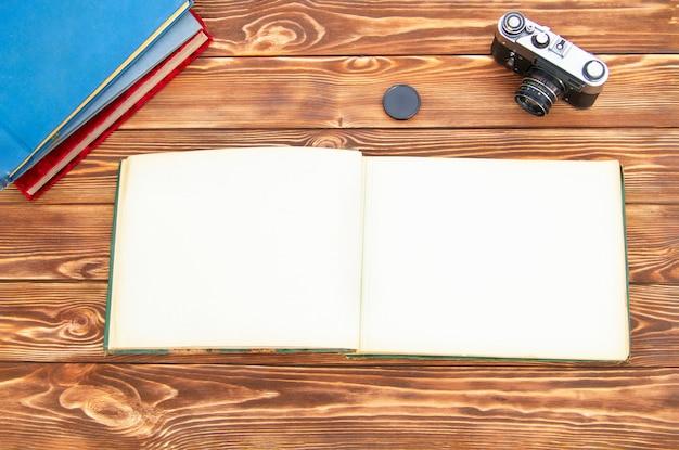 美しい茶色の木製テーブルと古いカメラの写真付きの古い写真アルバム。無料でモックアップ。コピースペース。