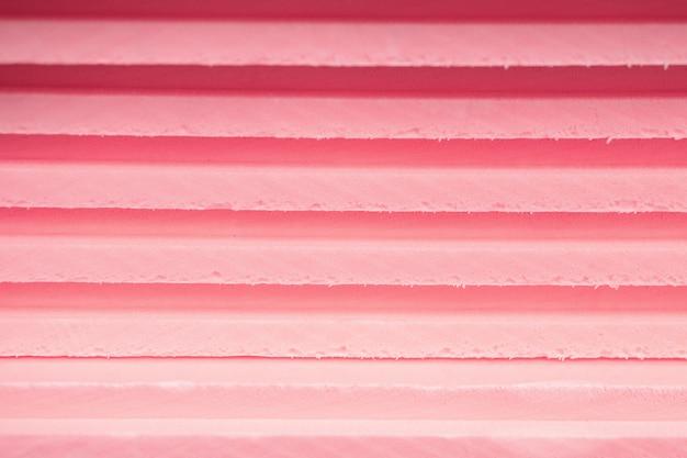 発泡断熱材の柔らかいシートは、ピンクと紫の異なる色合いの線で互いに重なり合っています。