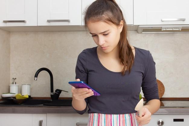 Готовим вкусную еду. девушка читает рецепт на смартфоне на кухне.