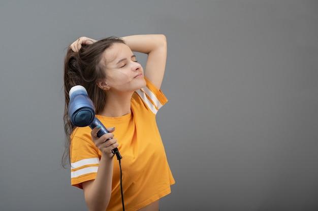 Парикмахерские и красивый стиль. молодая кавказская женщина сушит волосы феном
