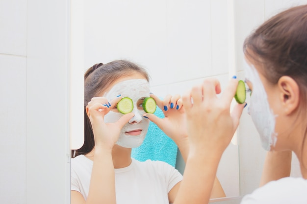 美容と健康。顔のスキンケア。若い女の子は、保湿クレンジングフェイスマスクになります