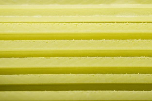 発泡断熱材の背景の柔らかいシートは、黄色の異なる色合いの線で互いに横たわっています