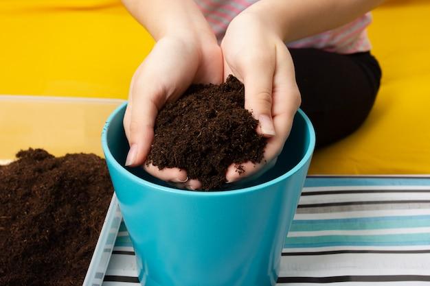 鍋に植物を植え直す少女