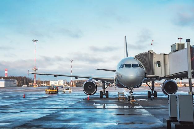 搭乗階段を備えた旅客機で、フライトの空港旅行の前に搭乗客と荷物を待っています。