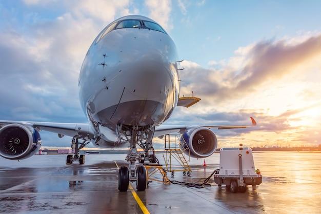 飛行前の飛行機、空港での航空機のメンテナンス。飛行場の夕日。
