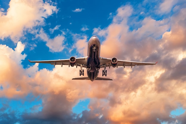 Вечернее небо с разбитыми красивыми облаками теплых тонов и самолет взлетает из аэропорта.
