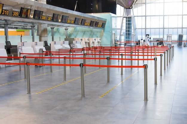 Пустой пассажирский терминал в аэропорту. пути ограничены и разделены красным полетом к стойке регистрации.