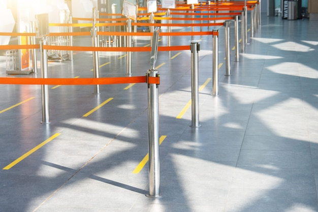 Пустые пути, ограниченные красной лентой, к стойкам регистрации и выдаче багажа на терминале пассажирского аэропорта.