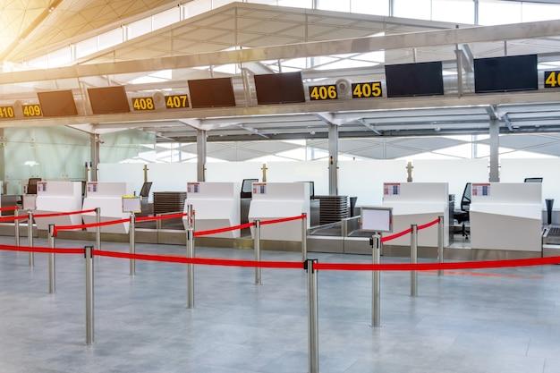 Пустые стойки регистрации для ручной клади, пути которых отменены красной лентой, чтобы разграничить пассажиров в терминале аэропорта.