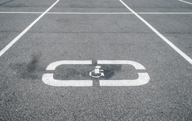 Стоянки для автомобилей, места для инвалидов, дорожный знак на асфальте.