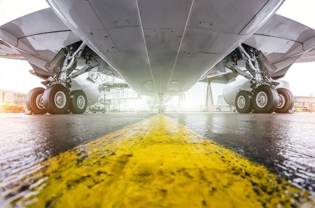 大型の旅客機が空港に停車し、下から見た翼と着陸装置。