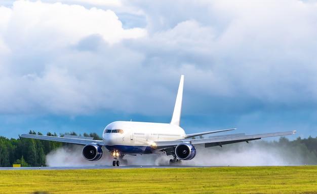 飛行機が空港で離陸し、雨が悪天候をはねかける