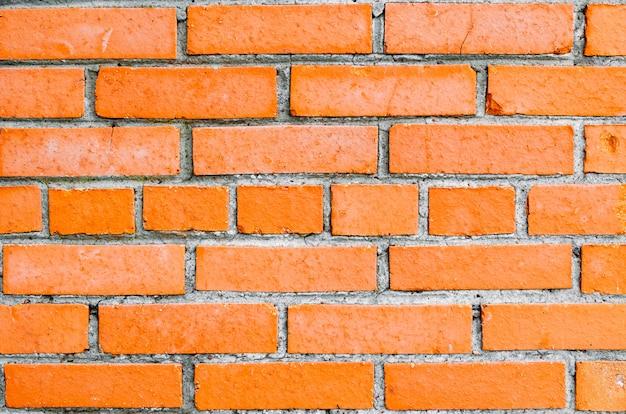 Кирпичная стена оранжевого кирпича, в среднем ряду кирпичей с прикладом.