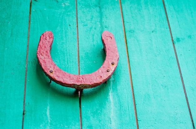 赤い木製の壁に古い幸運な蹄鉄。