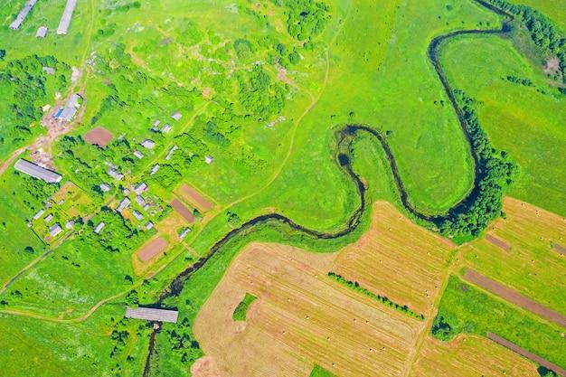 Верхний вид с воздуха естественного сельского ландшафта долины извилистой реки среди зеленых полей и лесов.