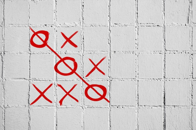 白いタイルのコンクリートの壁にチックタックトーゲーム