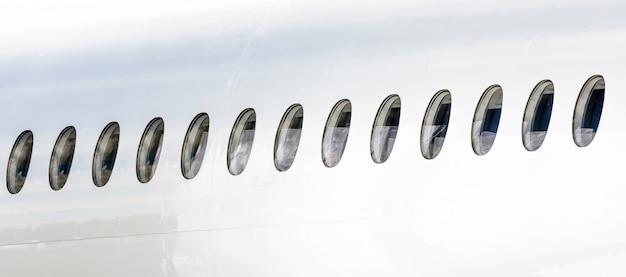 白い飛行機の胴体に並んでいる多くの舷窓。
