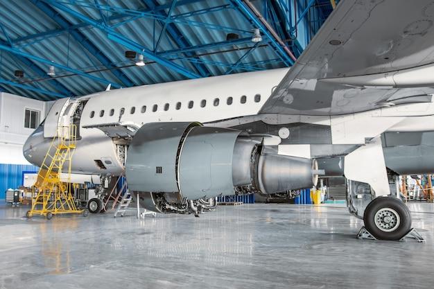 Узкий пассажирский самолет для обслуживания в ангаре, вид сбоку на двигатель и шасси.
