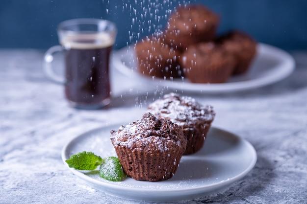 Шоколадные маффины с мятой на черной тарелке, посыпанные сахарной пудрой. домашняя выпечка. на заднем плане чашка кофе и тарелка с кексами. мраморный стол и синий фон.
