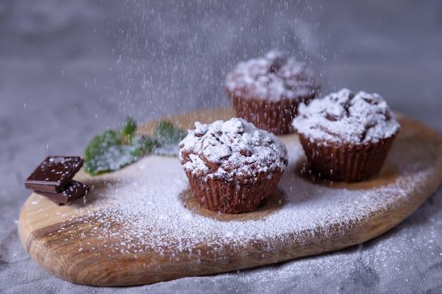 粉砂糖をまき散らした木の板にチョコレートのマフィン。自家製のベーキング。背景には一杯のコーヒーとマフィンのプレートがあります。木製の背景。セレクティブフォーカス、クローズアップ。