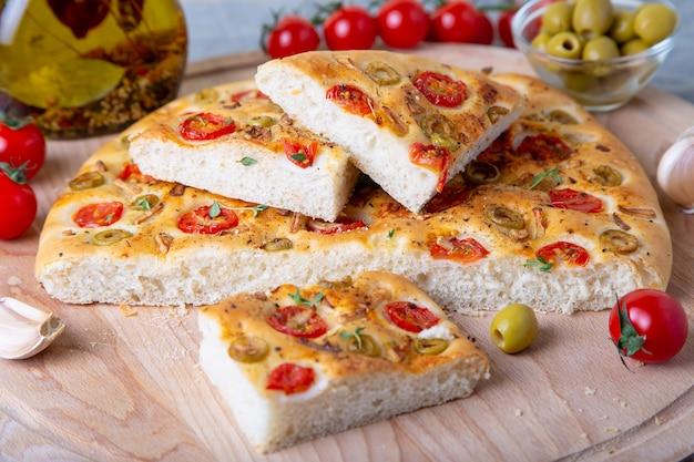 トマトとオリーブのフォカッチャ。伝統的なイタリアのパン。自家製のベーキング。クローズアップ、セレクティブフォーカス。