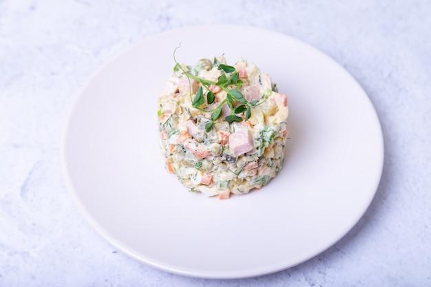 エンドウ豆の芽で飾られた白い皿にオリビエのサラダ。伝統的な新年とクリスマスのロシア風サラダ。クローズアップ、セレクティブフォーカス。