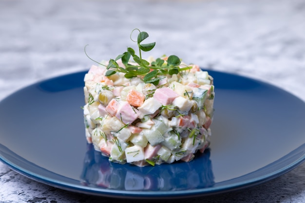 エンドウ豆の芽で飾られた青い皿の上のオリビエサラダ。伝統的な新年とクリスマスのロシア風サラダ。クローズアップ、セレクティブフォーカス。