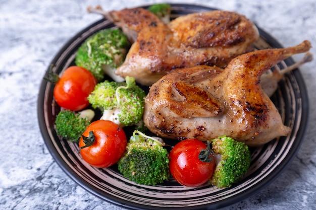 Перепелиное жареное целое с брокколи и помидорами черри. черная тарелка, мраморный фон. выборочный фокус, крупным планом.
