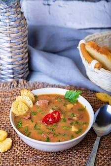 肉、スモークソーセージ、クルトン入りエンドウ豆のスープ。