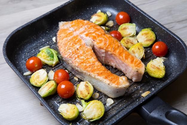 Стейк из лосося с брюссельской капустой, вишней и чесноком на сковороде. крупным планом, селективный фокус.