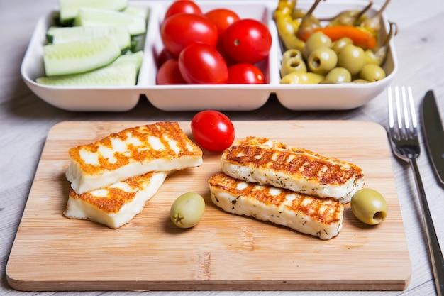 Жареный сыр халуми на деревянной доске с оливками, вишней, огурцами и пепперони. крупный план. выборочный фокус